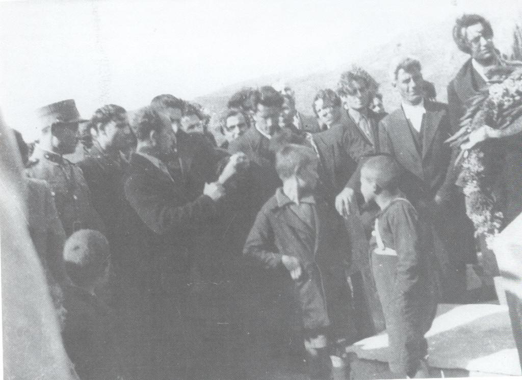 Ο επικήδειος πάνω από τον τάφο του Μ. Περλορέντζου. Τα αναστατωμένα μαλλιά των παρευρισκόμενων δείχνουν ότι φυσάει δυνατός αέρας
