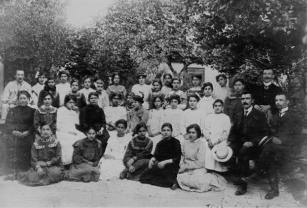 Ο Αλέξανδρος Δελμούζος (επάνω αριστερά) σε φωτογράφιση με μαθήτριες και καθηγητές του Παρθεναγωγείου Βόλου
