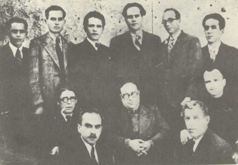 """«Ακροναυπλία 1941. Μετά την κατάργηση της Απομόνωσης, ύστερα από τους βομβαρδισμούς. Μέλη της Κομματικής Επιτροπής και της Επιτροπής της ομάδας. Καθιστοί από τ' αριστερά προς τα δεξιά: Κ. Θέος, Μήτσος Παπαρήγας, Γ. Ιωαννίδης, Μ. Λεβογιάννης, Β. Μπαρτζιώτας. Όρθιοι: Μαχαιρόπουλος, Λιανάς, Ζ. Ζωγράφος, Σ. Σουκαράς, Τ. Κουλαμπάς, Α. Μουζενίδης.» Πηγή φωτογραφίας: Κ. Θέου: """"Τα ελληνικά συνδικάτα στην πάλη ενάντια στο φασισμό και για την ανεξαρτησία τους"""", εκδ. """"Εργατικής"""", Αθήνα, Μάρτης 1947"""