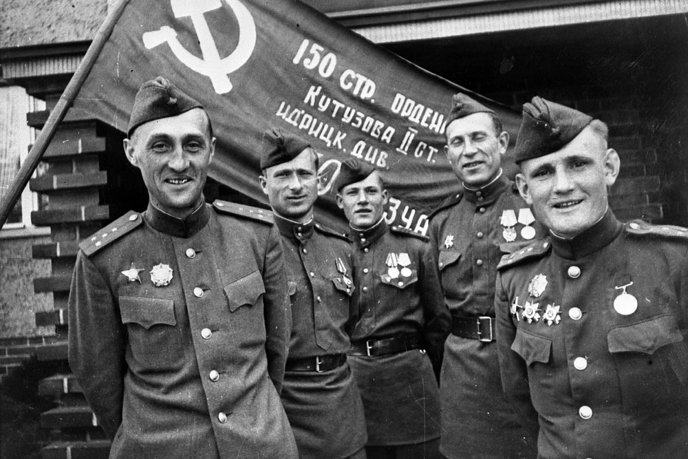 Ο Μελίτων Καντάρια (δεύτερος από δεξιά) μαζί με άλλους αξιωματικούς μπροστά στη Σημαία της Νίκης