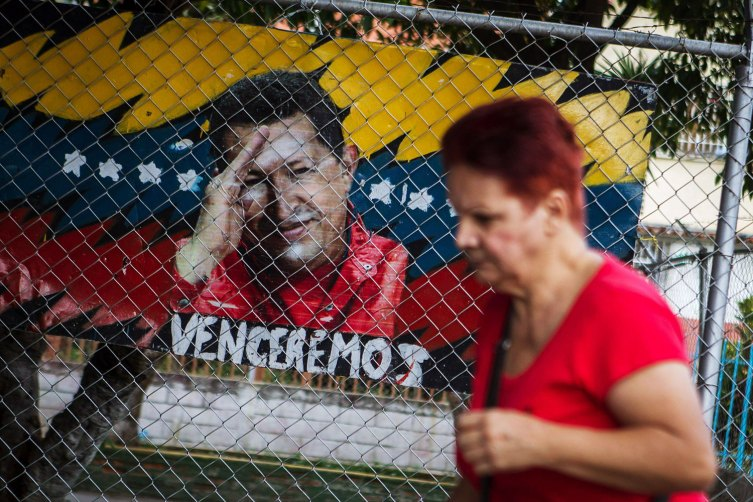 "02 January 2013 - Caracas, Venezuela - A woman walks next to a graffit paints of Venezuelan president Hugo Chavez in Caracas, Venezuela, on 02 January 2013. Venezuela remains uncertainty about news of health Chavez who is in Cuba, where just over 20 days was subjected to a ""complex"" surgery for a recurrence of cancer that was diagnosed in mid-2011. Photo Credit: Miguel Gutierrez/EFE/Sipa USA"