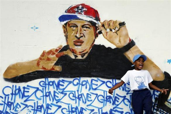 "A boy plays next to graffiti depicting Venezuelan President Hugo Chavez as a rap singer in Petare in the suburbs of Caracas September 13, 2012. In Venezuela's biggest slum, a graffiti artist stencils a painting of President Hugo Chavez dunking a basketball. Another has him rapping to hip-hop music, and another doing a wheelie on a motorcycle. ""Chavez el mio"" (""My Chavez"") reads a slogan on one of the series of striking campaign images ahead of the October 7 election. It is a new look for the 58-year-old president, who is seeking another six-year term in a tight race despite undergoing cancer surgery three times since June 2011. Picture taken September 13, 2012. To match Feature VENEZUELA-ELECTION/GHETTO REUTERS/Jorge Silva (VENEZUELA - Tags: POLITICS ELECTIONS SOCIETY)"