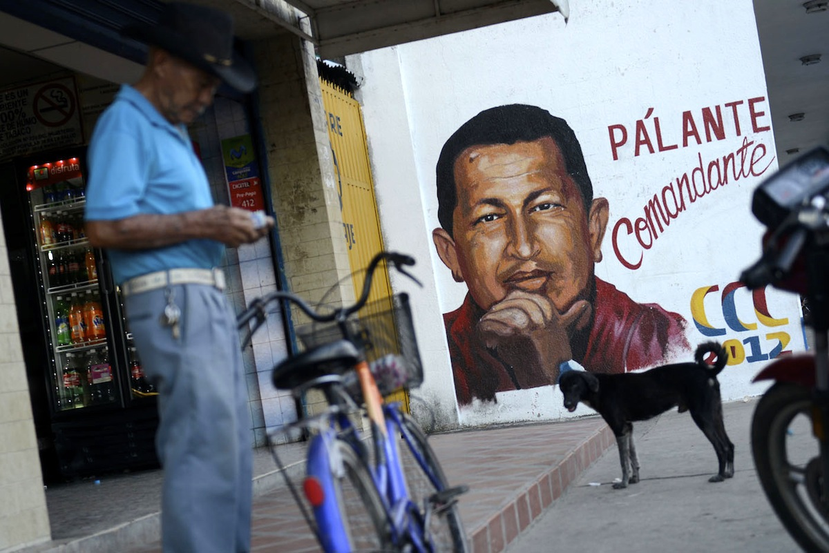 A man stands next to a campaign poster of Venezuelan President Hugo Chavez on September 26, 2012 in Sabaneta, Barinas, the birthplace of Chavez, ahead of the upcoming October 7th election. Chavez, in power since 1999, has easily won the last three presidential elections, and the latest poll shows the leftist leader holding a 10-point lead over opposition candidate Henrique Capriles. AFP PHOTO / Leo RAMIREZ