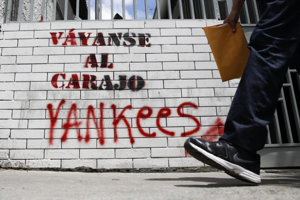 "A man walks past graffiti which reads ""Yankees, go to hell"" in Caracas March 10, 2015. REUTERS/Carlos Garcia Rawlins"