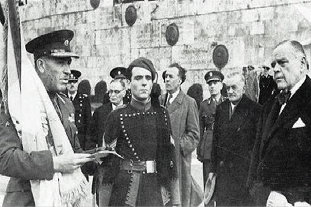 Ο συνεργάτης των Γερμανών «πρωθυπουργός»Ράλλης (δεξιά) και ο επικεφαλής των Ταγμάτων Ασφαλείας Αττικής Πλυτζανόπουλος (με τη σημαία), μπροστά στο μνημείο του Αγνώστου Στρατιώτη, επί Κατοχής…