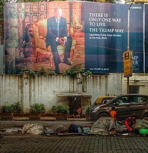 """ΒΟΜΒΑΗ, ΙΝΔΙΑ: Άστεγοι κοιμούνται στο πεζοδρόμιο σε φτωχογειτονιά της ασιατικής μεγαλούπολης με φόντο... διαφημιστική πινακίδα για τα προς πώληση υπερπολυτελή διαμερίσματα του ουρανοξύστη Trump Tower, ιδιοκτησίας του νέου προέδρου των ΗΠΑ. Κατά τραγική ειρωνεία, η διαφήμιση αναφέρει: """"Υπάρχει μόνο ένας τρόπος να ζεις."""