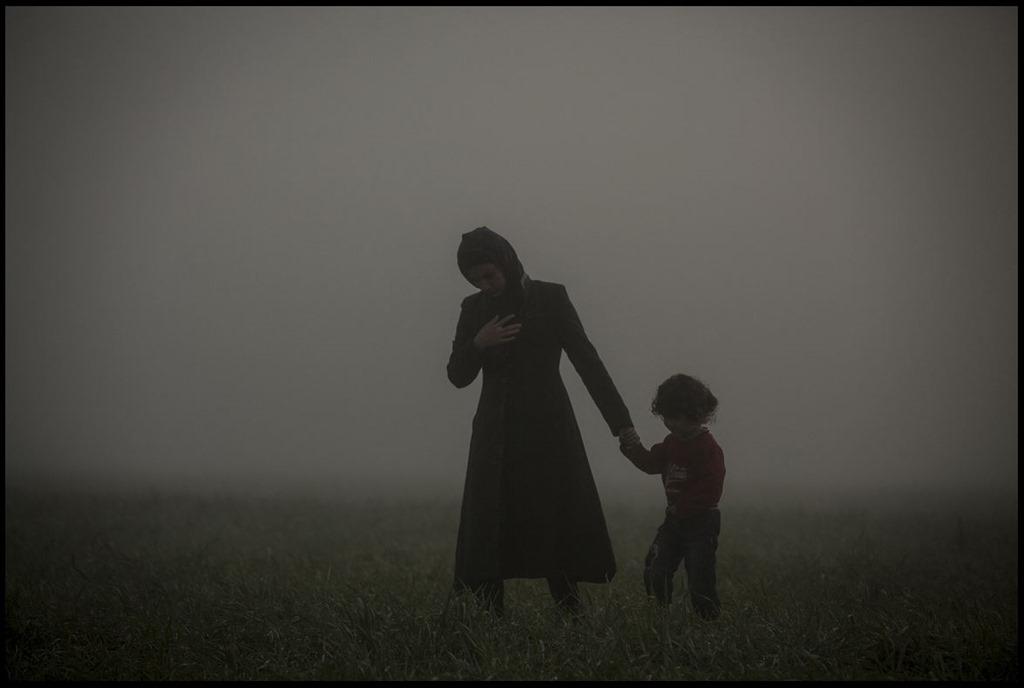 """Η μάνα με τον γιό της περπατούν γύρω από το αυτοσχέδιο στρατόπεδο προσφύγων - Ειδομένη 8/3/2016 Η φωτογραφία του Olmo Calvo τιμήθηκε με το πρώτο βραβείο στην κατηγορία General News για το έτος 2016 από τον διεθνή οργανισμό διαγωνισμού φωτορεπορτάζ """"Pictures of the Year International"""""""