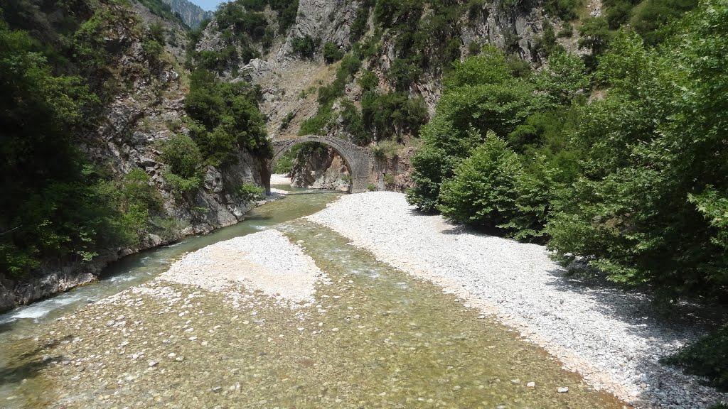 Η γέφυρα του Λιάσκοβου είναι ένα εντυπωσιακό μονότοξο πετρογέφυρο με άνοιγμα τόξου 17 μ. και ύψος 11 μ., μέσα σε θαυμάσιο φυσικό και άγριο περιβάλλον, το φαράγγι του Πετριλιώτη. Βρίσκεται στον δρόμο για Συκιά και Πηγές Άρτας, στη θέση «Γέρακας» ή «Πυρήνα» Πετρωτού. Γεφυρώνει τα ρέματα Κουμπουργιανίτικο και Πλατανιά, λίγο πριν την ένωσή τους με τον Αχελώο. Εικασίες θέλουν το γεφύρι να κτίστηκε τον 13ο αιώνα. Χρυσοθήρες έσκαψαν το κατάστρωμα της γέφυρας για να βρουν θησαυρό και μετακίνησαν δεκάδες πέτρες, με αποτέλεσμα από τα νερά της βροχής και την υγρασία να υπάρχει διάβρωση και πρόβλημα την στατική του κατάσταση.