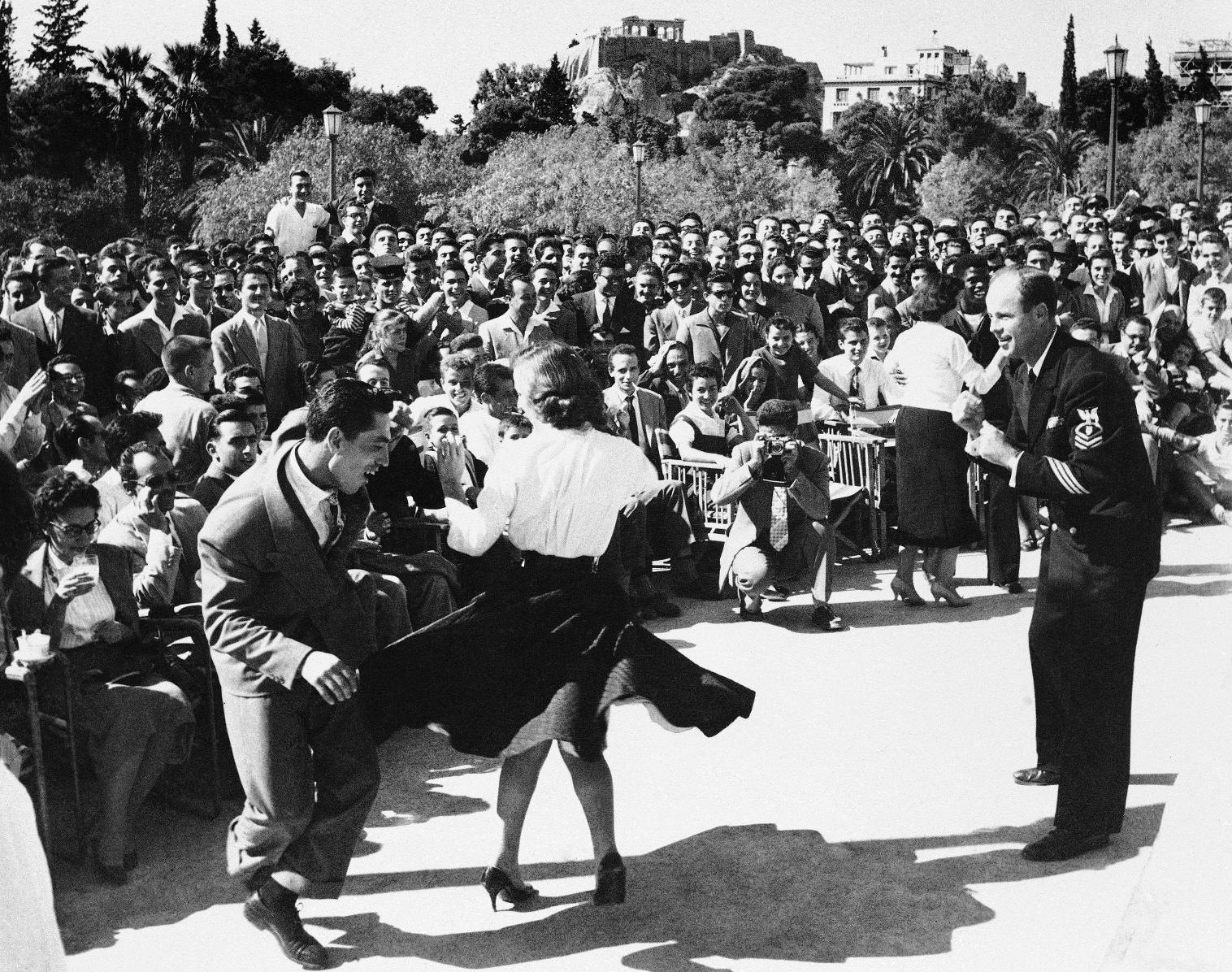 Έλληνες νεολαίοι χορεύουν στους ξέφρενους ρυθμούς του Ροκ εντ ρολ κατά τη διάρκεια συναυλίας της μπάντας του αμερικανικού στόλου στην Αθήνα, το 1957. (AP Photo) - Πηγή Καθημερινή