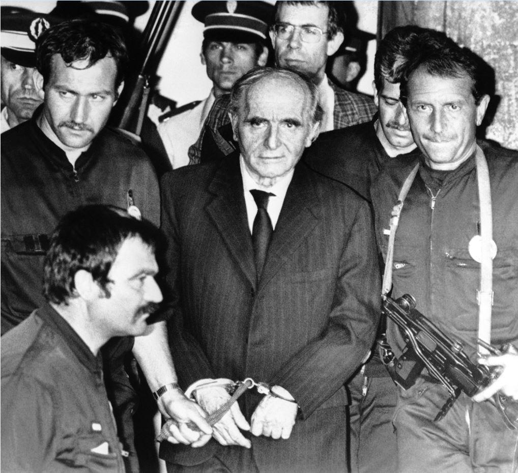 Γάλλοι αστυνομικοί συνοδεύουν έξω από την αίθουσα του δικαστηρίου τον δεμένο με χειροπέδες, εγκληματία πολέμου και πρώην αξιωματούχο του Τρίτου Ράιχ, Κλάους Μπάρμπι, μετά την καταδίκη του σε θάνατο για εγκλήματα πολέμου κατά τη διάρκεια της θητείας του ως επικεφαλής της Γκεστάπο στη Λυών την περίοδο της γερμανικής κατοχής της Γαλλίας, το 1988. Τα εγκλήματα πολέμου του Μπάρμπι τον κατέγραψαν στη γαλλική συλλογική μνήμη ως «Χασάπη της Λυών».