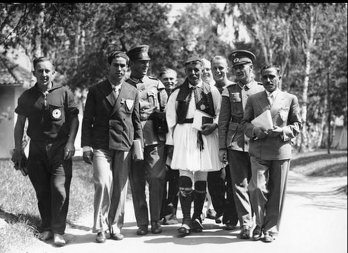Μέλη της ελληνικής αποστολής και Γερμανοί αστυνομικοί συνοδεύουν τον Σπύρο λούη στο Ολυμπιακό Χωριό του Βερολίνου