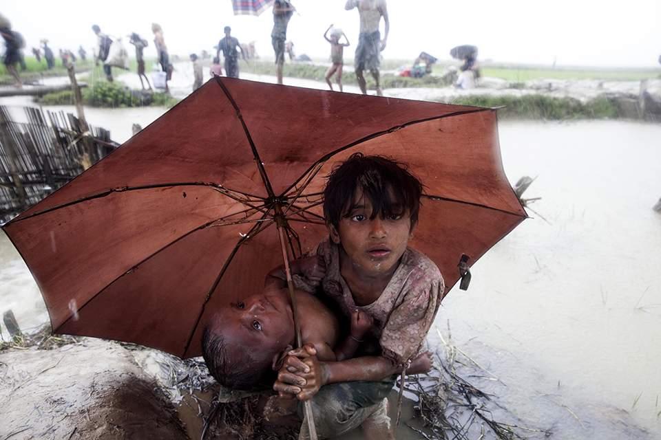 Δύο παιδιά Rohingya ξαποσταίνουν εν μέσω βροχής στα ριζοχώραφα κοντά στα σύνορα της Μιανμάρ με το Μπαγκλαντές στο οποίο προσπαθούν να βρουν καταφύγιο (Πηγή φωτό: Καθημερινή)