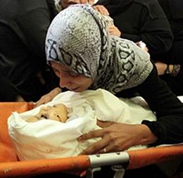 Μητέρα αποχαιρετά το νεκρό βρέφος-θύμα βομβαρδισμών.