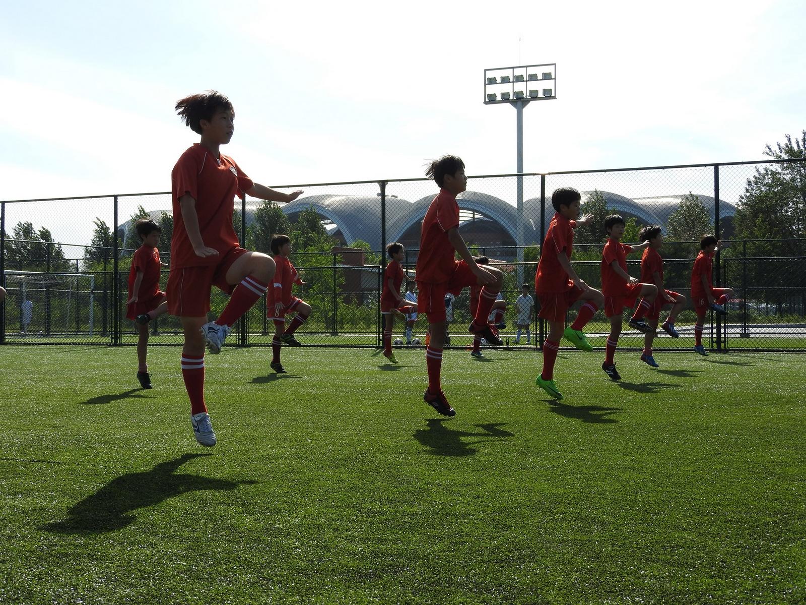 Ζέσταμα και ασκήσεις γυμναστικής νεαρών αθλητών στη  Διεθνή Ποδοσφαιρική Ακαδημία της Πιονγιάνγκ, με εγκαταστάσεις  που δεν έχουν να ζηλέψουν τίποτα από αυτές δυτικών χωρών.
