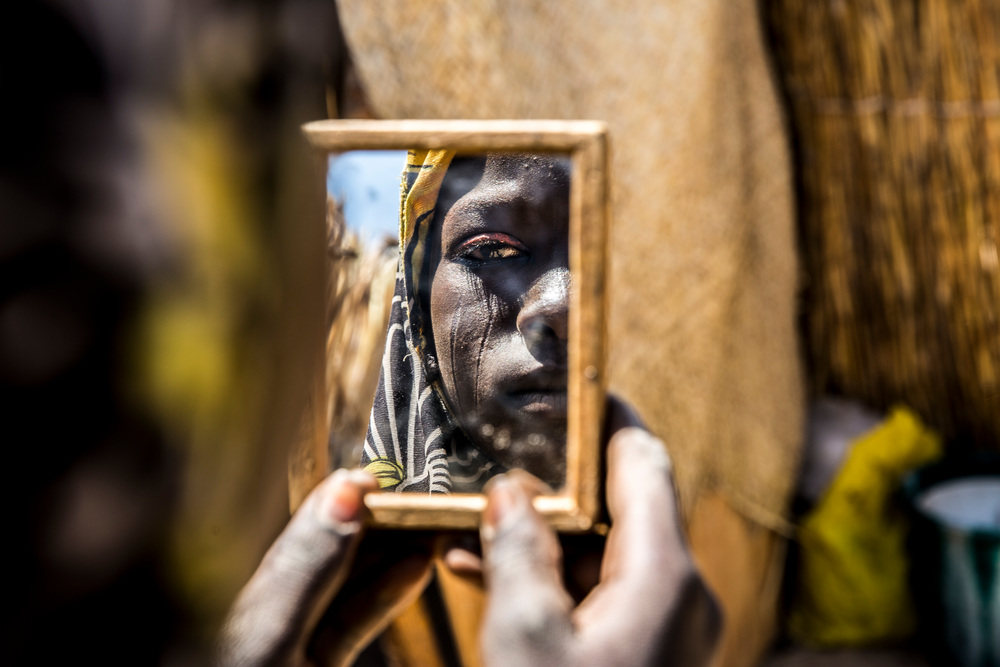 Νιγηρία: Στην επαρχία Ντίφα του νοτιοανατολικού Νίγηρα, που μαστίζεται από τη βία της Μπόκο Χαράμ, μια γυναίκα κοιτάζεται στον καθρέφτη. Το βλέμμα της γεμάτο απόγνωση. Έφτασε στην κλινική των Γιατρών Χωρίς Σύνορα για προγεννετική φροντίδα. Ο σύζυγός της λαμβάνει φροντίδα ψυχικής υγείας. (Φεβρουάριος 2017). πηγη: Juan Carlos Tomasi/MSF