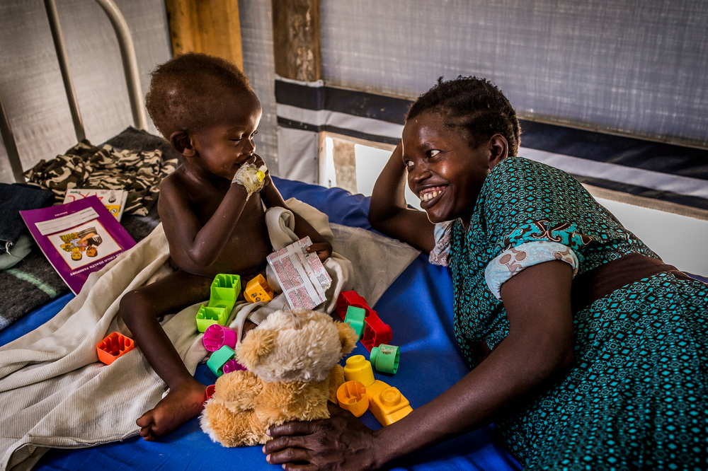 Ουγκάντα: Στο τμήμα ασθενών του Μπιντιμπίντι στη μονάδα των Γιατρών Χωρίς Σύνορα για την καταπολέμηση του υποσιτισμού ένα παιδί απολαμβάνει μερικές στιγμές χαράς, παίζοντας μαζί με τη μητέρα του. (Απρίλιος 2017). πηγη: Frederic NOY/COSMOS