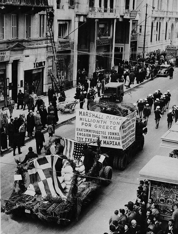 Το ελληνικό κράτος τιμά με παρελάσεις στο κέντρο της Αθήνας τις Ηνωμένες Πολιτείες για την οικονομική ενίσχυση που δέχεται η χώρα στο πλαίσιο του σχεδίου Μάρσαλ, μετά το τέλος του εμφυλίου πολέμου, το 1949. (AP Photo) - Πηγή Καθημερινή