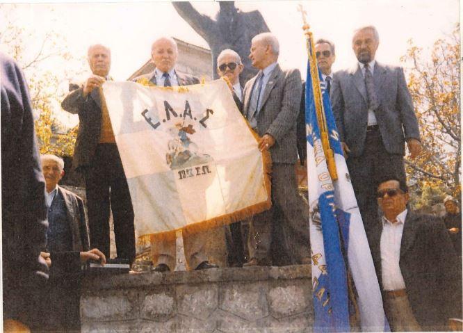 Καλέντζι, Κυριακή 2 του Μάη 1993… Βαθειά συγκίνηση των παρευρισκομένων την ώρα που οι πρωταντάρτες του 12ου Συντάγματος καπετάν Ρήγας και κ. Πορευόπουλος ξεδιπλώνουν την ιστορική σημαία. Διακρίνονται ο πρόεδρος της ΠΟΑΕΑ κ. Τσοπανίδης, ο πρόεδρος της κοινότητας Καλεντζίου κ. Πετρόπουλος και κάτω διακρίνεται ο κ. Βλάσσης Βελλόπουλος.