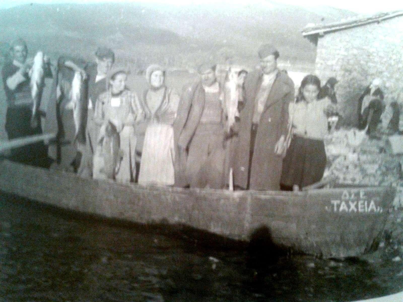 """Ντόπιοι κάτοικοι των Πρεσπών με μαχητές του ΔΣΕ επιδεικνύουν την ψαριά του στη βάρκα """"ΔΣΕ Ταχεία""""."""