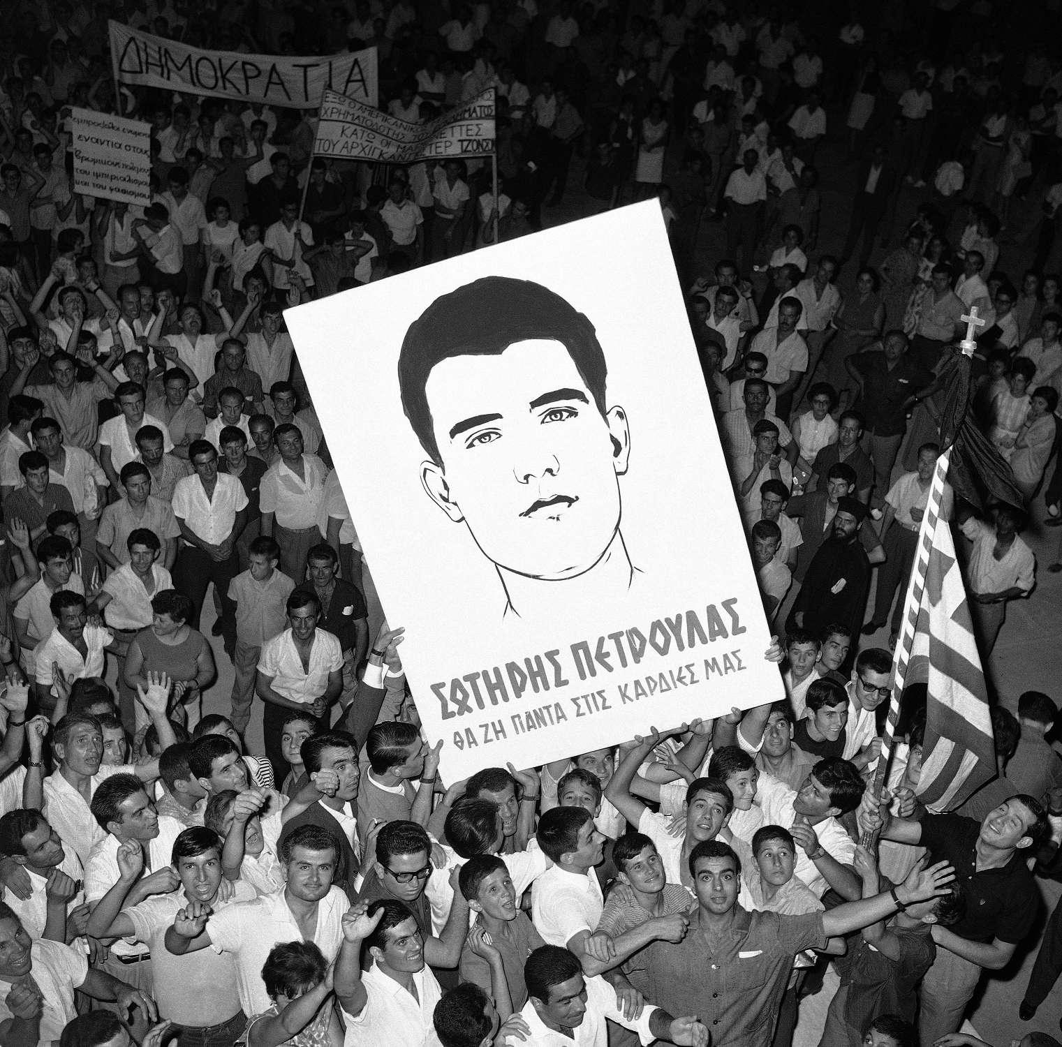 «Σωτήρης Πέτρουλας – Θα ζη πάντα στις καρδιές μας», γράφει ένα πλακάτ με το πορτρέτο του προσφάτως δολοφονηθέντος φοιτητή, σε διαδήλωση στη Θεσσαλονίκη, τρεις μέρες μετά το θάνατο του, κατά την περίοδο των Ιουλιανών του 1965