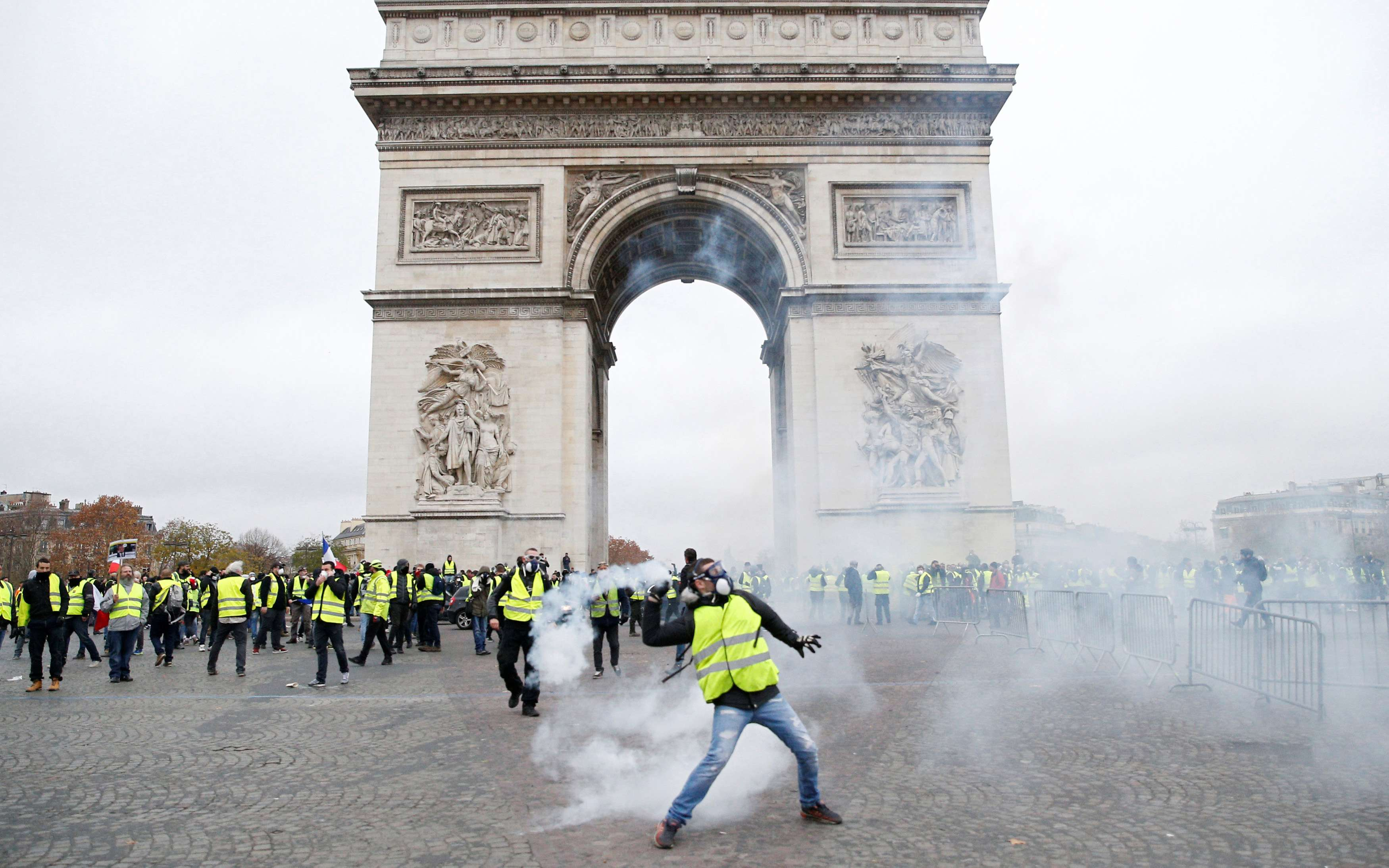 Tear gas floats in the air near the Arc de Triomphe as protesters wearing yellow vests, a symbol of a French drivers' protest against higher diesel taxes, demonstrate in Paris, France, December 1, 2018. REUTERS/Stephane Mahe