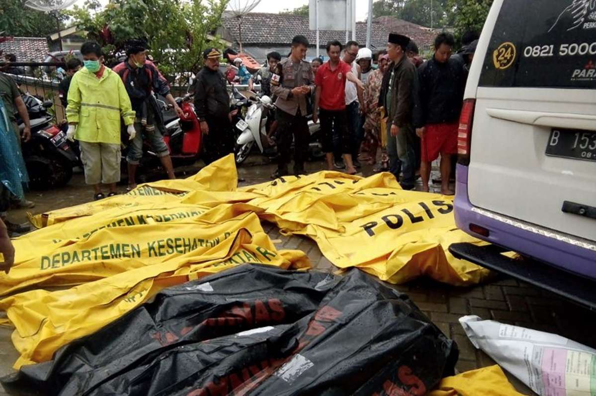 Bodies of victims recovered along Carita beach are placed in body bags on December 23, 2018, after the area was hit by a tsunami on December 22 following an eruption of the Anak Krakatoa volcano. - A tsunami following a volcanic eruption killed 62 people and injured hundreds more as it slammed without warning into tourist beaches and coastal areas around Indonesia's Sunda Strait on the night of December 22, sending panicked holidaymakers and residents fleeing. (Photo by Semi / AFP)