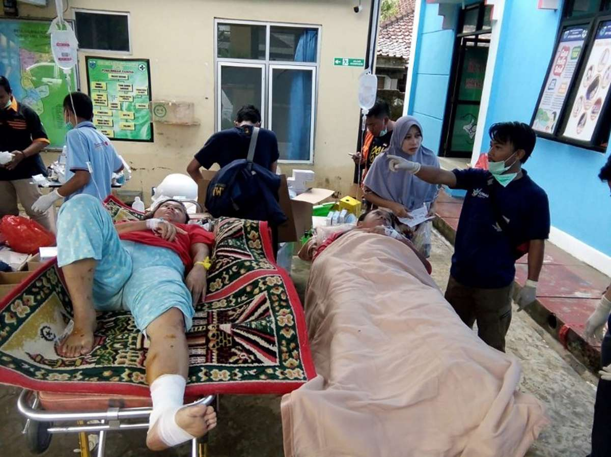 Survivors receive treatment at a hospital in Carita on December 23, 2018, after the area was hit by a tsunami on December 22 following an eruption of the Anak Krakatoa volcano. - A tsunami following a volcanic eruption killed 62 people and injured hundreds more as it slammed without warning into tourist beaches and coastal areas around Indonesia's Sunda Strait on the night of December 22, sending panicked holidaymakers and residents fleeing. (Photo by Semi / AFP)