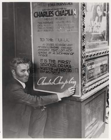 Chaplin signs a poster for A Woman of Paris