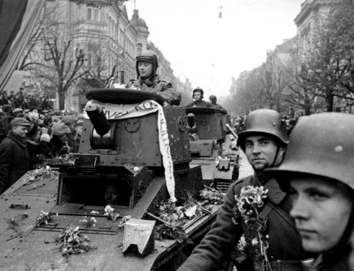 Lithuanian soldiers triumphantly parade though Vilnius as citizens throw flowers and display the Lithuanian flag